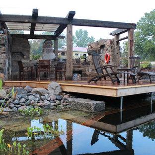 Foto de piscina con fuente natural, rural, de tamaño medio, a medida, en patio trasero, con entablado