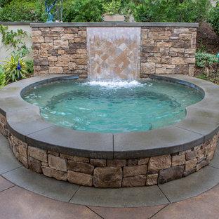Hot tub - large mediterranean backyard custom-shaped and concrete paver hot tub idea in Orange County