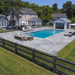 Imagen de piscina alargada, campestre, grande, rectangular, en patio trasero, con adoquines de piedra natural