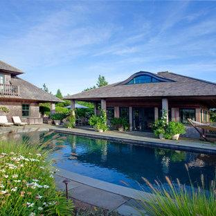 Diseño de piscina alargada, bohemia, de tamaño medio, rectangular, en patio trasero, con adoquines de hormigón