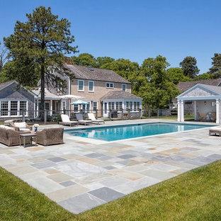 Großes Landhaus Sportbecken hinter dem Haus in rechteckiger Form mit Natursteinplatten und Poolhaus in Boston