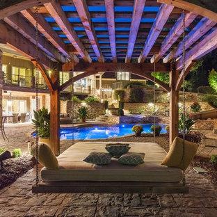 Foto di un'ampia piscina minimalista personalizzata dietro casa con un acquascivolo e pavimentazioni in pietra naturale