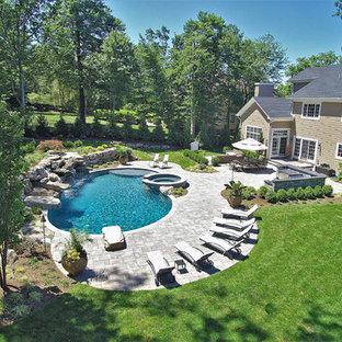 """Idee per una grande piscina monocorsia tropicale a """"C"""" dietro casa con una vasca idromassaggio e pavimentazioni in pietra naturale"""