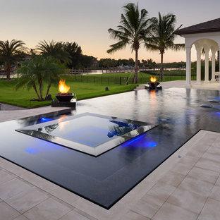 Diseño de piscinas y jacuzzis infinitos, actuales, grandes, a medida, en patio trasero, con suelo de baldosas