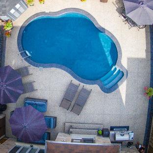 Diseño de piscina tradicional renovada, pequeña, tipo riñón, en patio trasero, con suelo de hormigón estampado