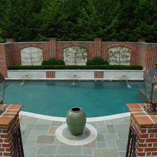 This is an example of a mid-sized arts and crafts courtyard custom-shaped natural pool in Atlanta with a water feature and natural stone pavers.