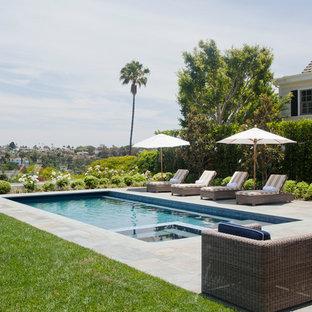 Modelo de piscinas y jacuzzis alargados, clásicos, de tamaño medio, rectangulares, en patio trasero, con suelo de baldosas