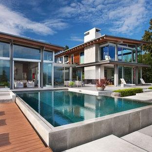 Modelo de piscina elevada, actual, extra grande, rectangular, en patio trasero, con losas de hormigón