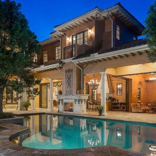 Large tuscan backyard stone and rectangular infinity pool photo in Orlando