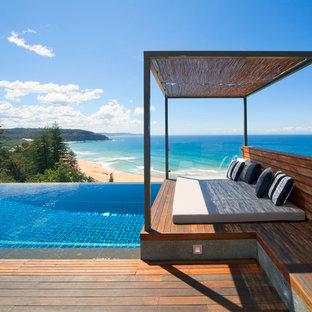 Стильный дизайн: маленький бассейн-инфинити в современном стиле с настилом - последний тренд