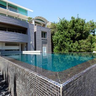 Immagine di un'ampia piscina monocorsia moderna personalizzata dietro casa con pedane