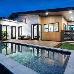 Foto de piscina alargada, retro, grande, rectangular, en patio trasero, con entablado