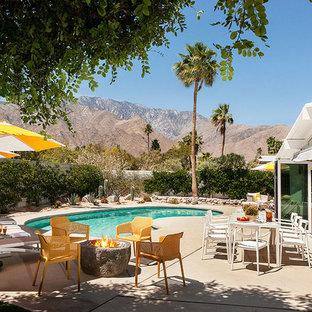 Ejemplo de piscina vintage, tipo riñón, en patio trasero, con losas de hormigón