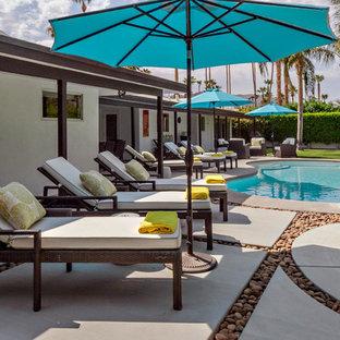 Imagen de piscina minimalista, grande, tipo riñón, en patio trasero, con losas de hormigón