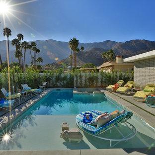 Imagen de piscina vintage, de tamaño medio, rectangular, en patio trasero, con losas de hormigón
