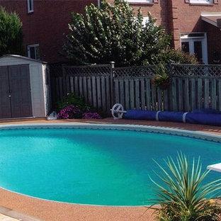 Ejemplo de piscina alargada, de tamaño medio, tipo riñón, en patio trasero, con granito descompuesto
