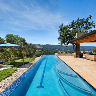 Ejemplo de piscinas y jacuzzis alargados, de estilo americano, grandes, rectangulares, en patio trasero, con suelo de baldosas