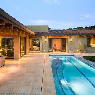 На фото: большой спортивный, прямоугольный бассейн на заднем дворе в стиле фьюжн с покрытием из плитки с