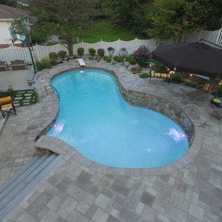 Foto de piscinas y jacuzzis naturales, clásicos, de tamaño medio, a medida, en patio trasero, con adoquines de ladrillo