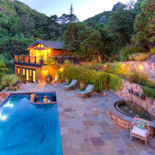 This is an example of an arts and crafts side yard rectangular pool in San Francisco with a water feature and natural stone pavers.