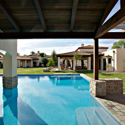 Example of a large tuscan backyard tile and custom-shaped lap pool design in Phoenix