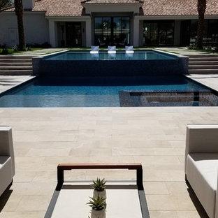 Ejemplo de casa de la piscina y piscina alargada, contemporánea, grande, rectangular, en patio trasero, con adoquines de piedra natural