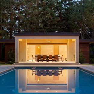 Modelo de casa de la piscina y piscina alargada, minimalista, grande, rectangular, en patio trasero, con suelo de hormigón estampado