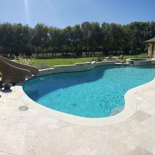 Esempio di una grande piscina naturale minimalista personalizzata dietro casa con un acquascivolo e pedane