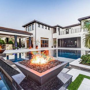 На фото: прямоугольный бассейн-инфинити на заднем дворе в современном стиле
