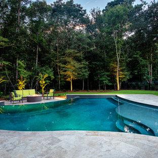 Ejemplo de piscina infinita, clásica renovada, de tamaño medio, a medida, en patio trasero, con adoquines de piedra natural