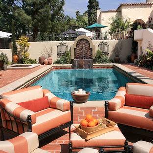 Foto di una piscina monocorsia mediterranea rettangolare di medie dimensioni e dietro casa con una vasca idromassaggio e pavimentazioni in mattoni