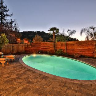 Ejemplo de piscina natural, campestre, a medida, en patio trasero, con adoquines de hormigón