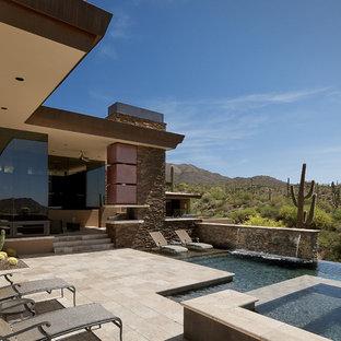 Ejemplo de piscinas y jacuzzis infinitos, de estilo americano, grandes, a medida, en patio trasero, con adoquines de piedra natural