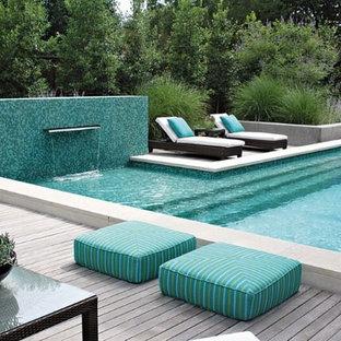 Idee per una grande piscina monocorsia design rettangolare dietro casa con pedane