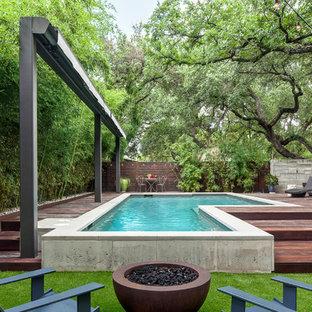Immagine di una piscina moderna personalizzata di medie dimensioni e dietro casa con pedane