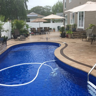 Example of a mid-sized classic backyard tile and kidney-shaped aboveground pool design in New York