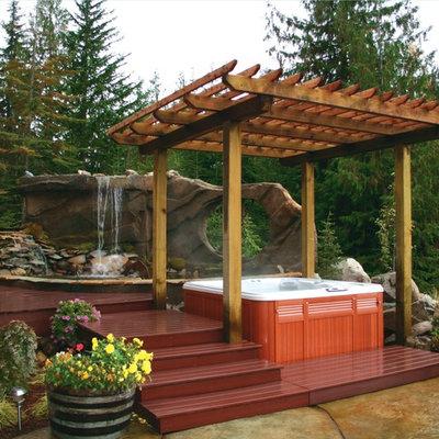Large island style backyard rectangular aboveground hot tub photo in Boise with decking