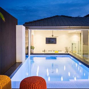 Immagine di una piscina monocorsia minimal rettangolare di medie dimensioni e dietro casa con pedane