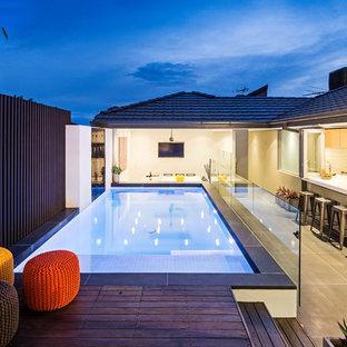 Idee per una piscina design rettangolare di medie dimensioni e dietro casa con pedane