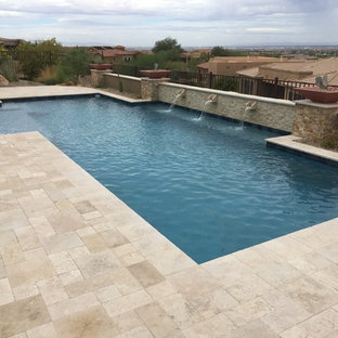 This is an example of a mid-sized transitional backyard rectangular lap pool in Phoenix with a water feature and natural stone pavers.