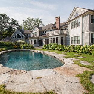Foto de piscina clásica, redondeada, con adoquines de piedra natural