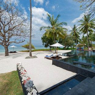 """Immagine di una piscina naturale stile marino a """"L"""" di medie dimensioni e in cortile con una dépendance a bordo piscina e piastrelle"""