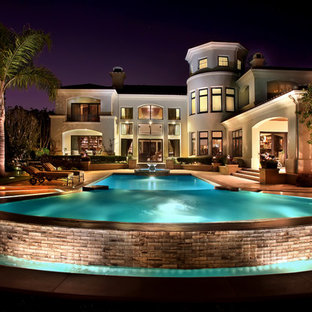 Design ideas for a large traditional backyard custom-shaped infinity pool in Orange County with a water feature and natural stone pavers.