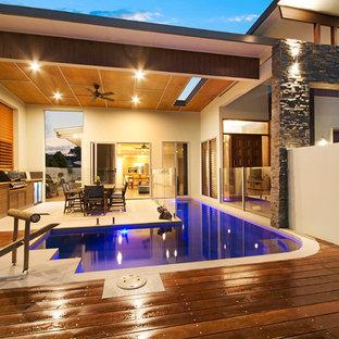 Modelo de piscina de estilo zen, de tamaño medio, en forma de L, en patio delantero, con suelo de baldosas