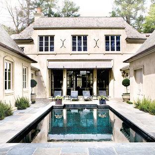 Idee per una grande piscina monocorsia chic rettangolare in cortile con pavimentazioni in pietra naturale