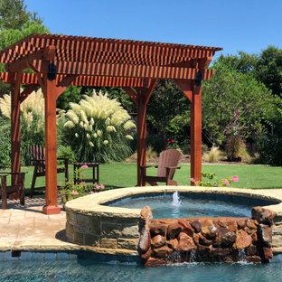 Modelo de piscinas y jacuzzis rústicos, tipo riñón, en patio trasero, con adoquines de ladrillo