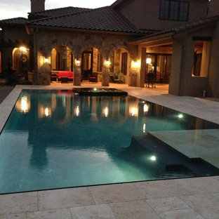 Hot tub - large mediterranean backyard stone and rectangular infinity hot tub idea in Austin