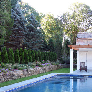 Design ideas for a small country side yard rectangular pool in New York with a pool house and natural stone pavers.
