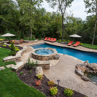 Large arts and crafts backyard custom-shaped pool in Kansas City with a water feature and concrete slab.