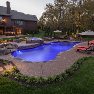 Example of a large arts and crafts backyard concrete and custom-shaped hot tub design in Kansas City
